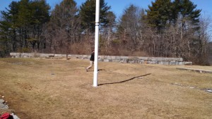 "Flagpole viewed from ""tee"" 14. Player is shown throwing second shot after laying up around the flagpole mandatory."